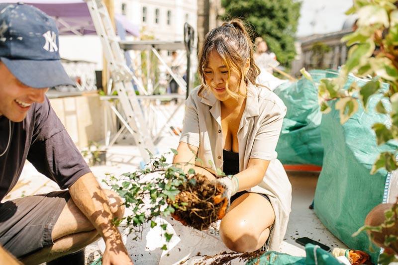 Woman planting flowers in Gaia's Garden
