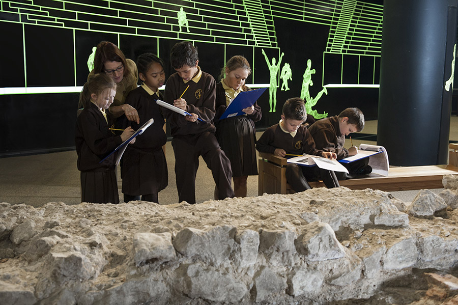Children writing notes on clipboards in amphitheatre