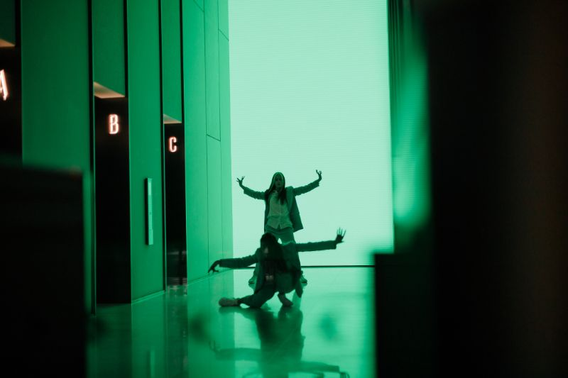 Dancers in an office building illuminated in green lighting