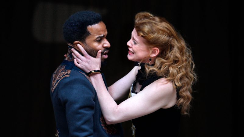 A female actor holds a male actor's face in a production of Shakespeare