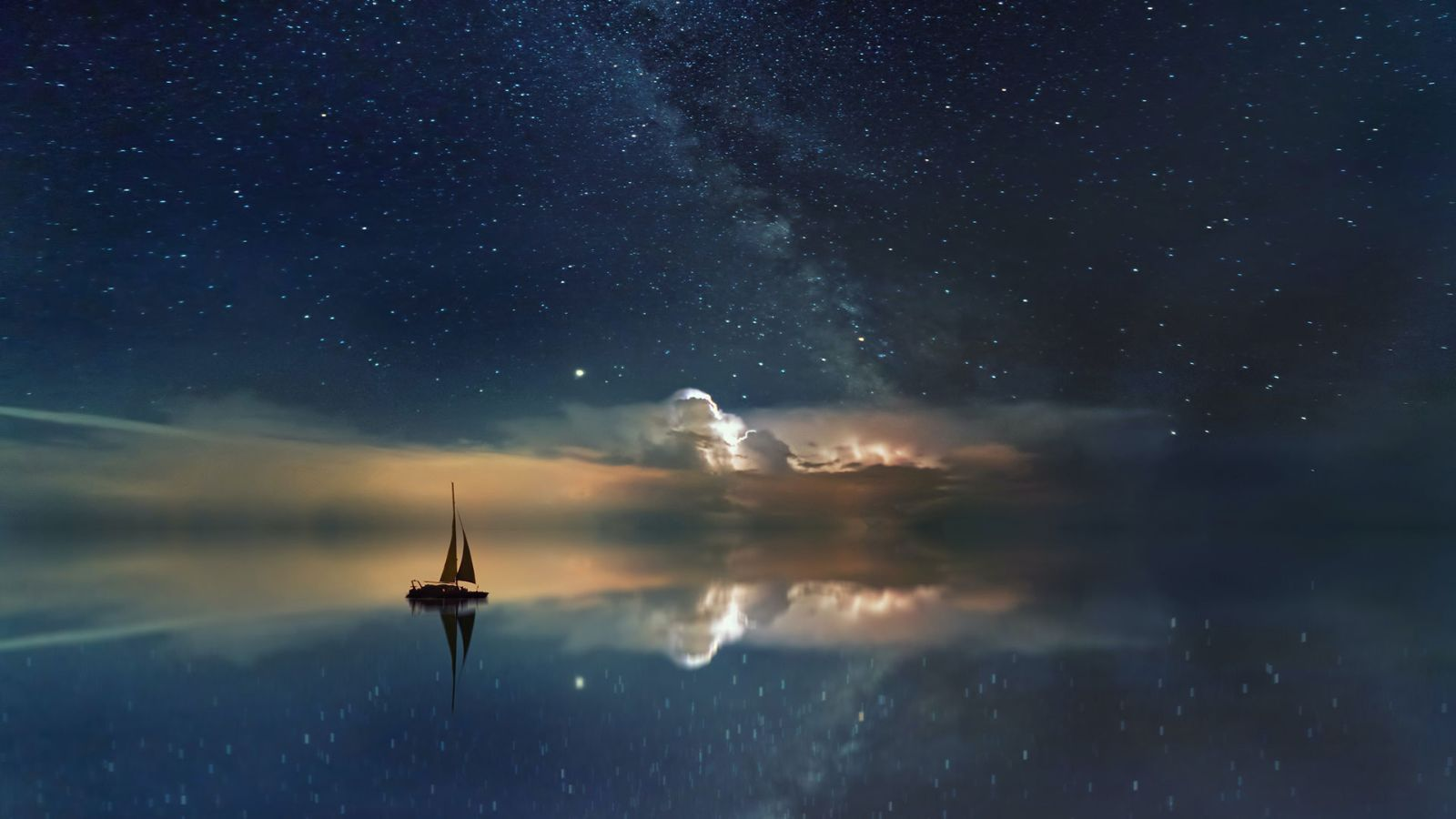 A sail boat with stars and clouds in the night sky in the backgr