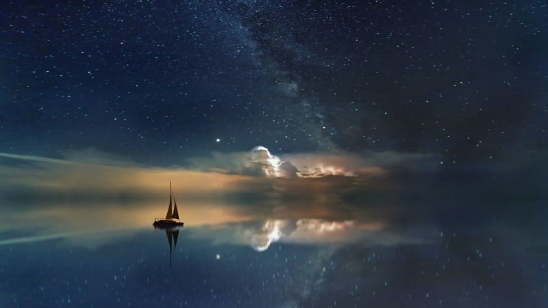 A sail boat with stars and clouds in the night sky in the background