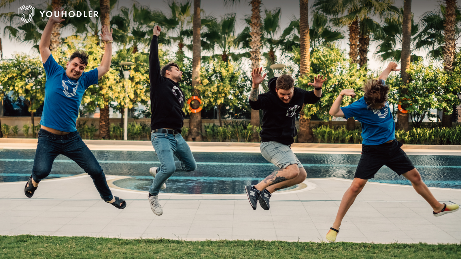 the youhodler team jumps in mid-air, arms raised in celebration.