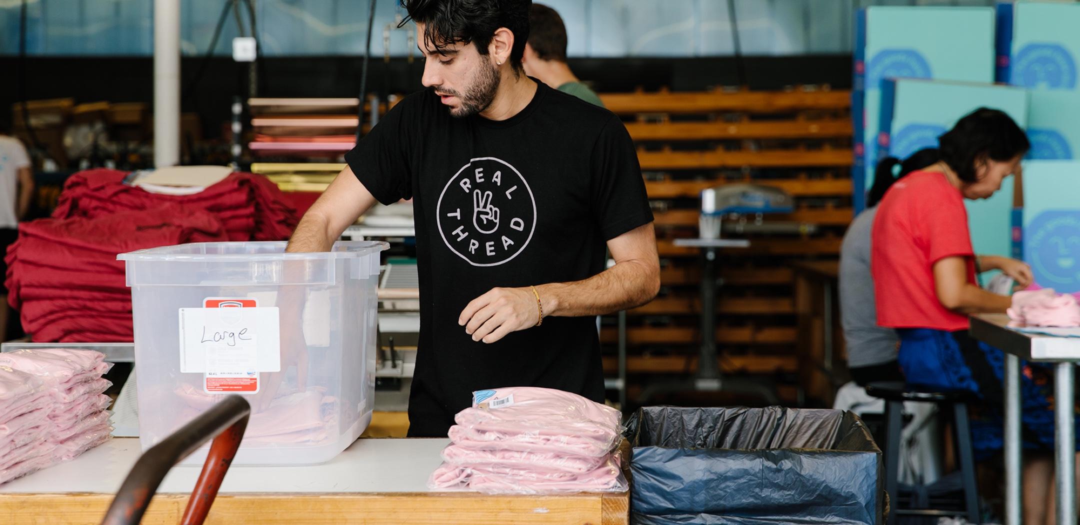 A man starts packaging an order of custom t-shirts.