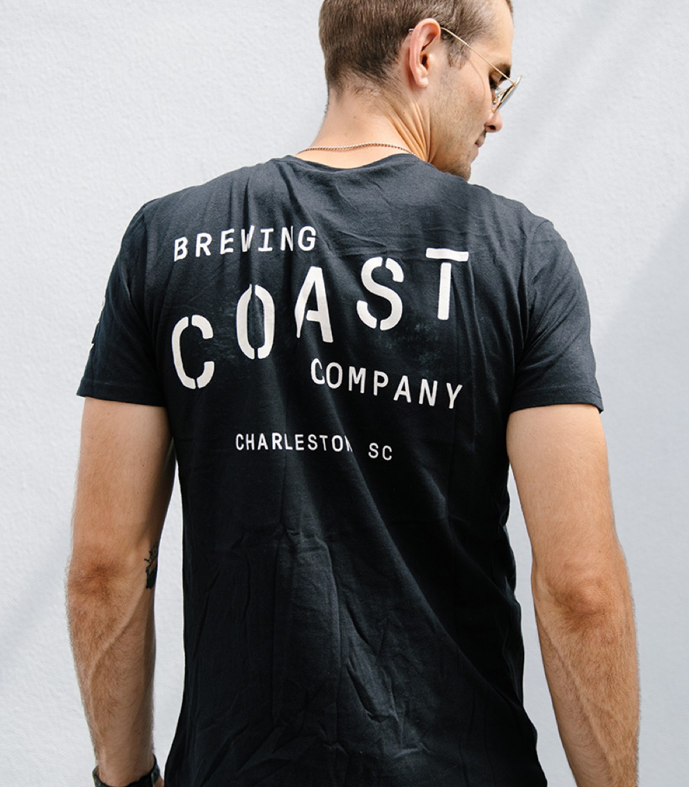 A man wears a trendy black and white brewing company shirt.