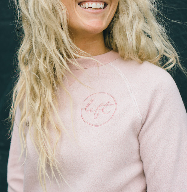 Blonde haired girl wearing a light pink fuzzy sweater with custom embroidery