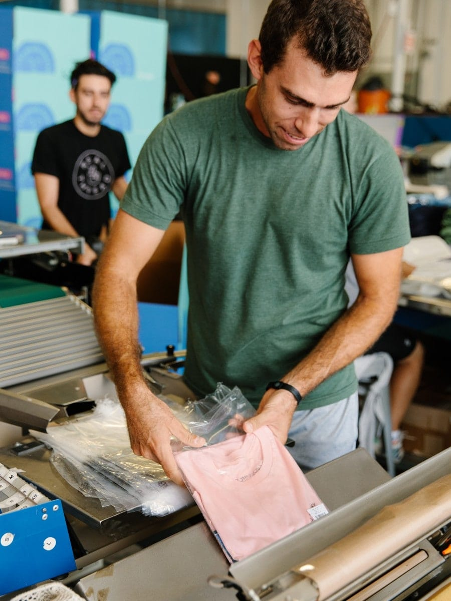 A man prepares a shirt for fulfillment, packing it in a polybag to keep it tidy.