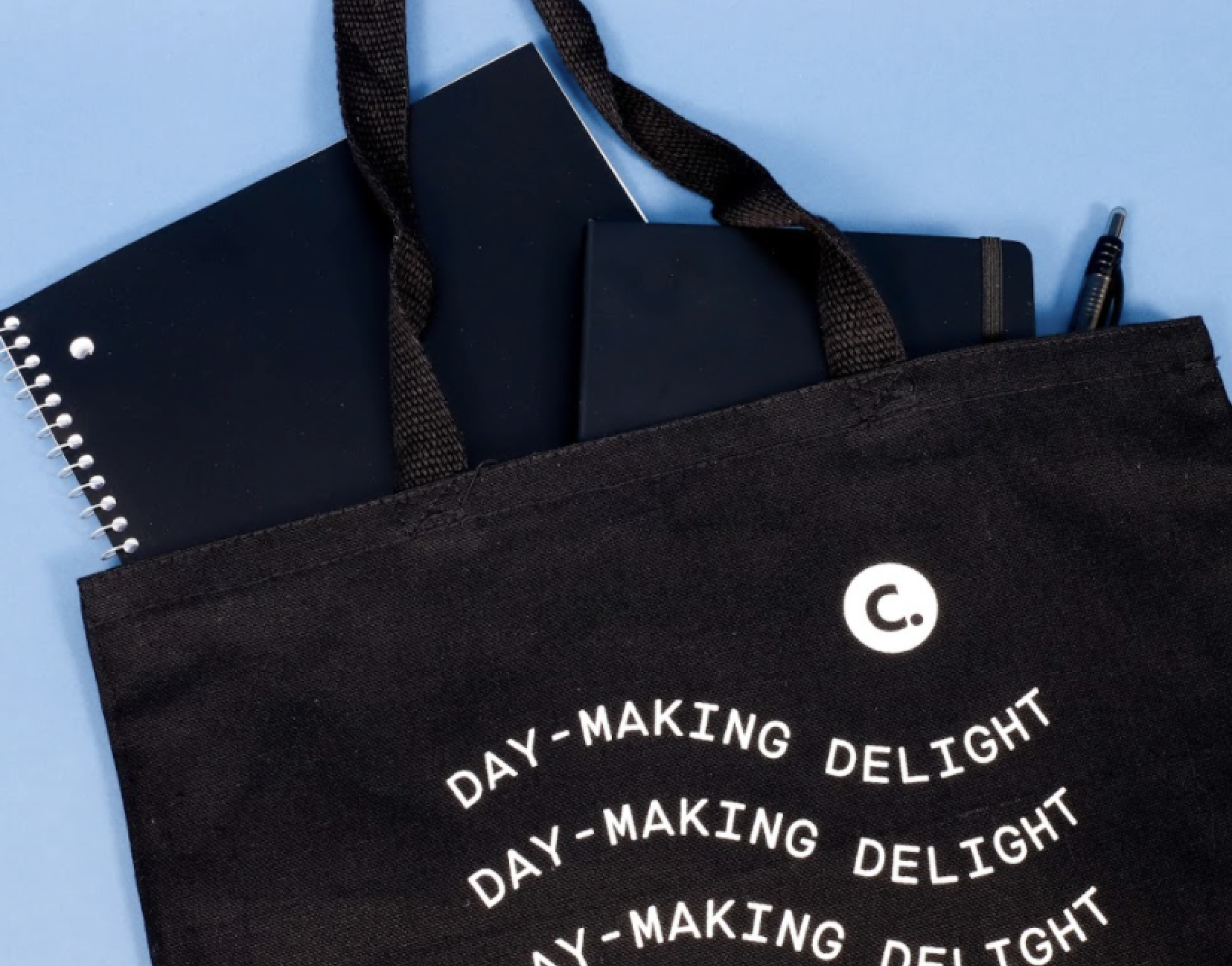A Corkcicle tote bag filled with pens, notebook, and more.