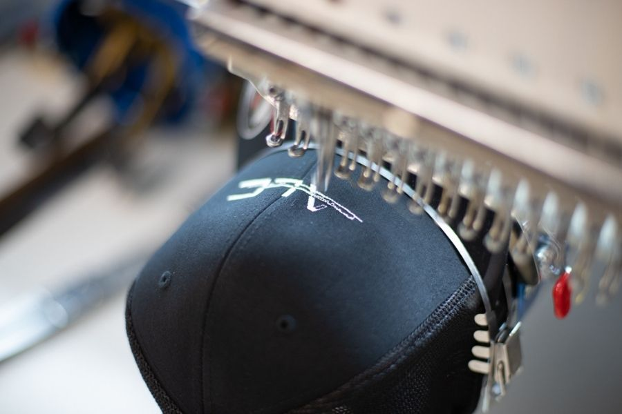 The needle punctures the hat to embroider it
