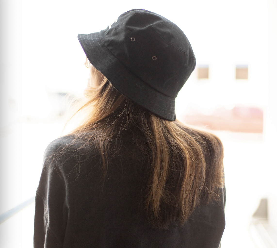 A brown haired girl wearing a bucket hat looks off into the distance.