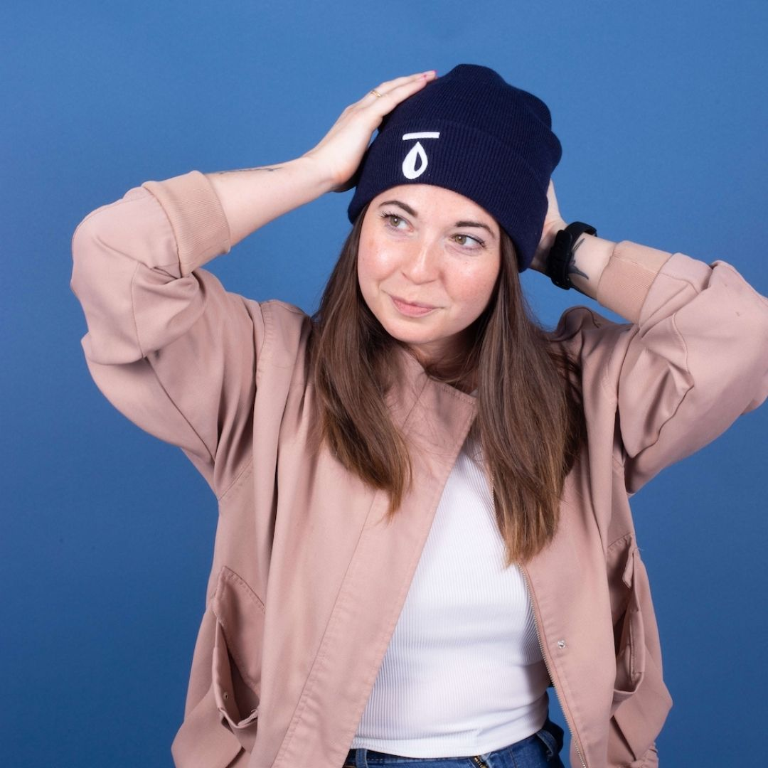 A brown haired girl adjusts her waterdrop logo beanie.