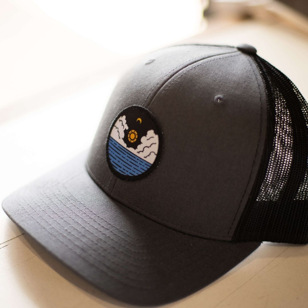 A custom embroidered patch of a sunrise over the water is on the front of this snapback hat.