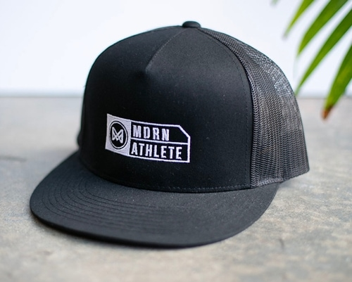 A black snapback hat with custom white embroidery