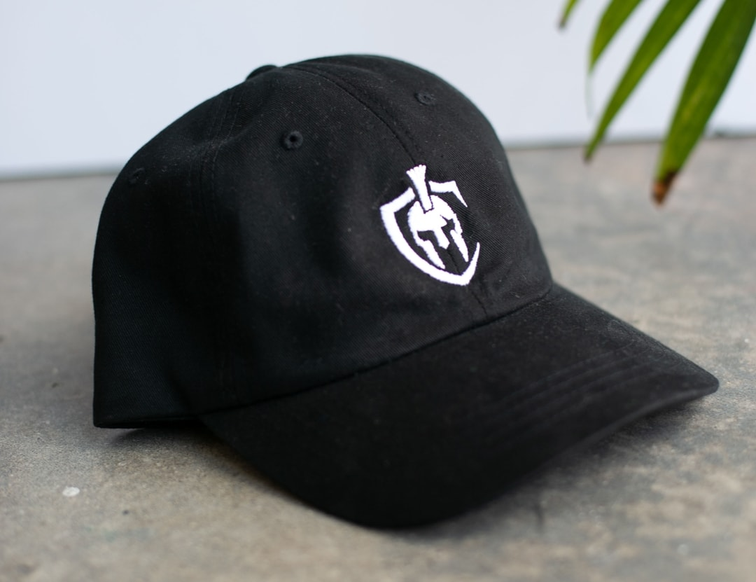 A black dad hat with white embroidery sits on a concrete floor.