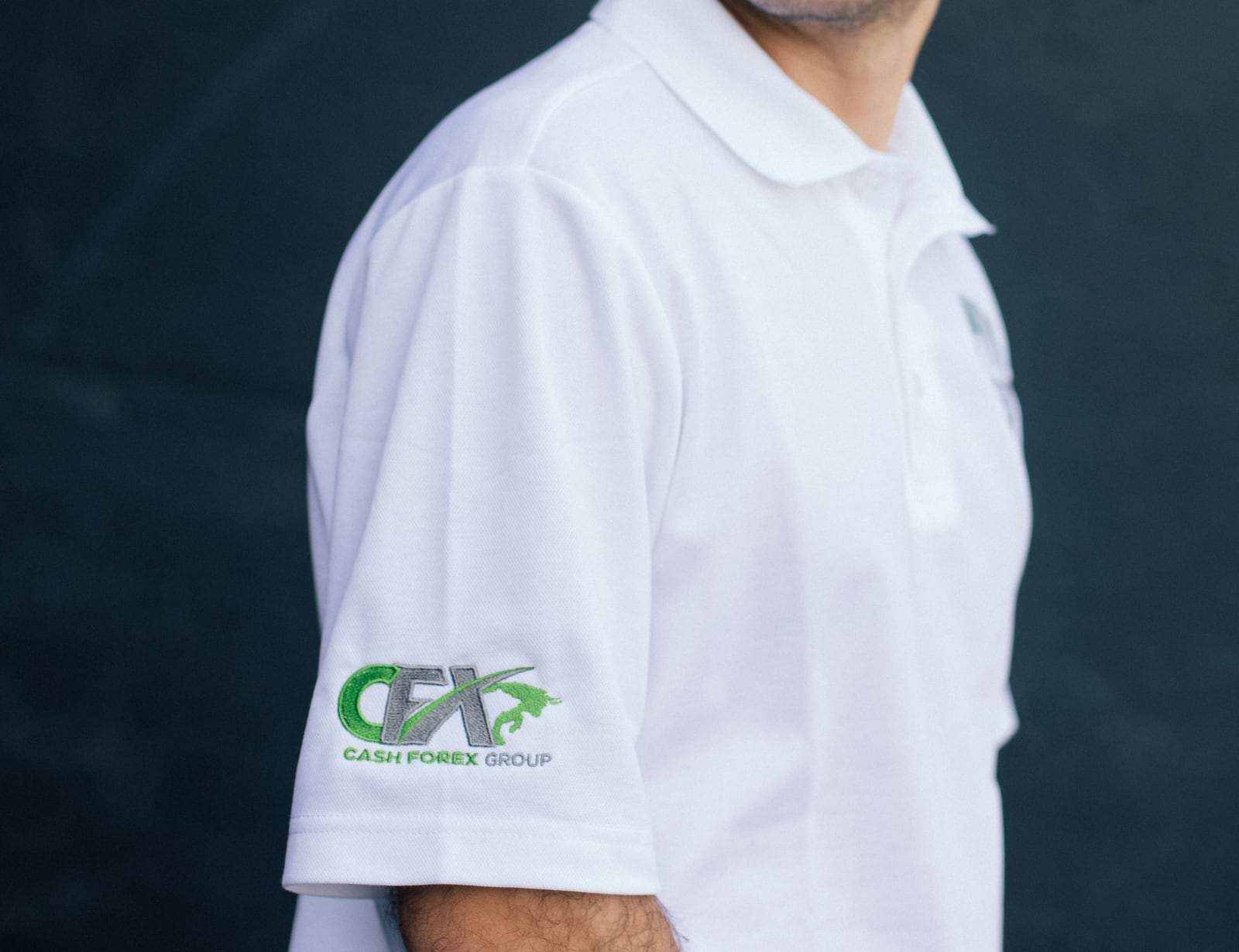 A white polo with custom embroidery on the front chest and sleeve