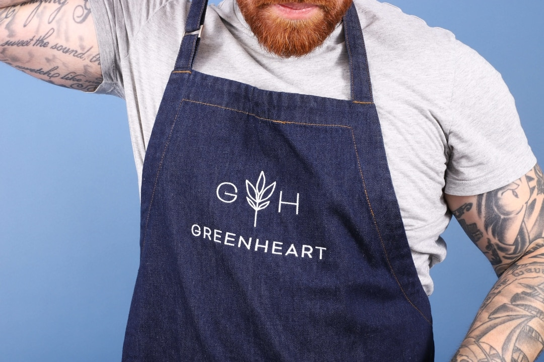 A man with tattoos wears a denim apron with custom white embroidery