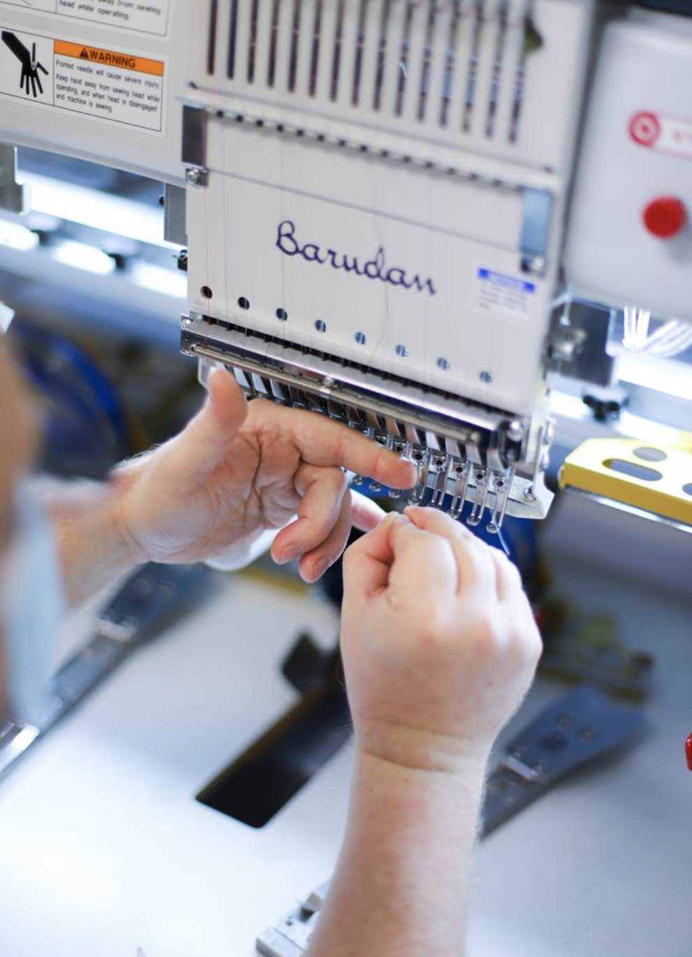Man threads needle for embroidery machine