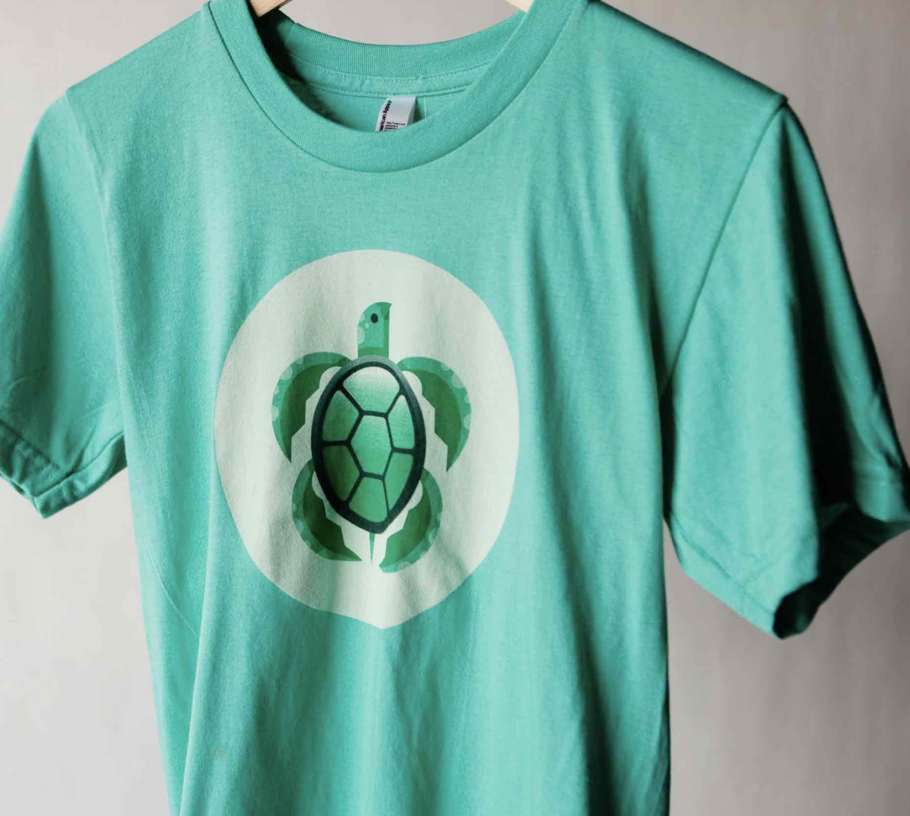 An eco-friendly green shirt with a cute little turtle on the front, printed with water based inks