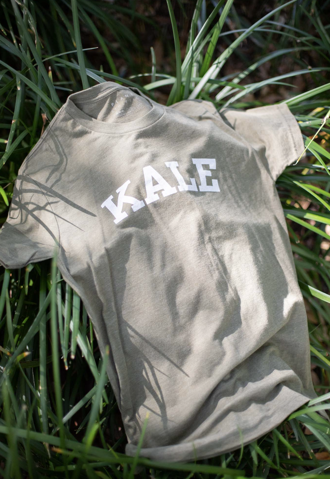"""A shirt that reads """"kale"""" is laying artfully in the grass."""