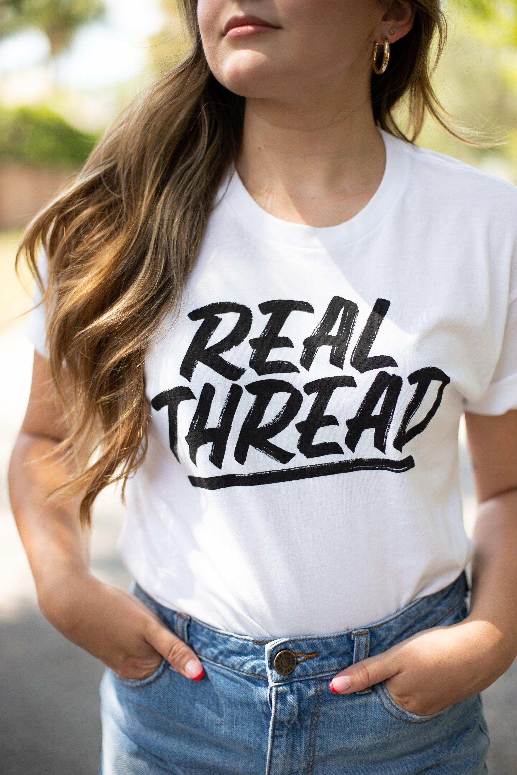 A girl wears a white Real Thread custom printed t-shirt.