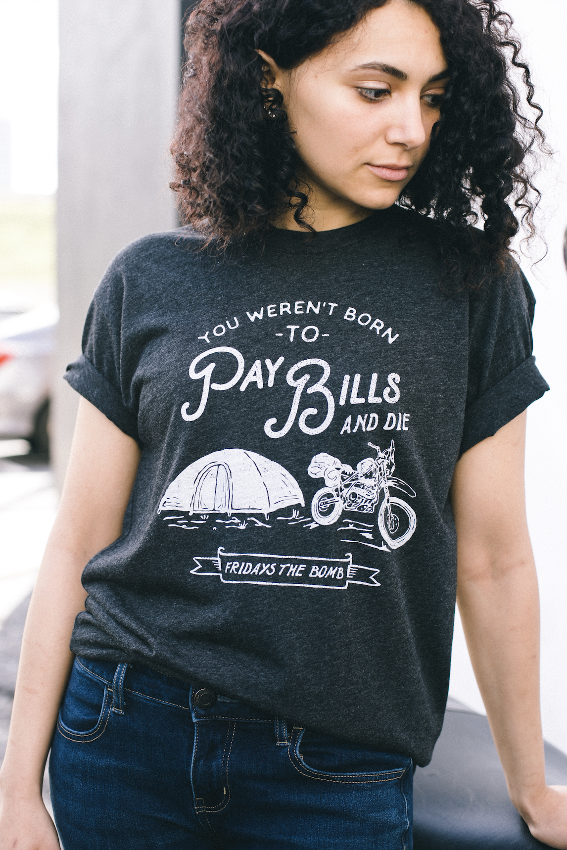 A curly-haired girl wears a dark gray custom printed t-shirt.