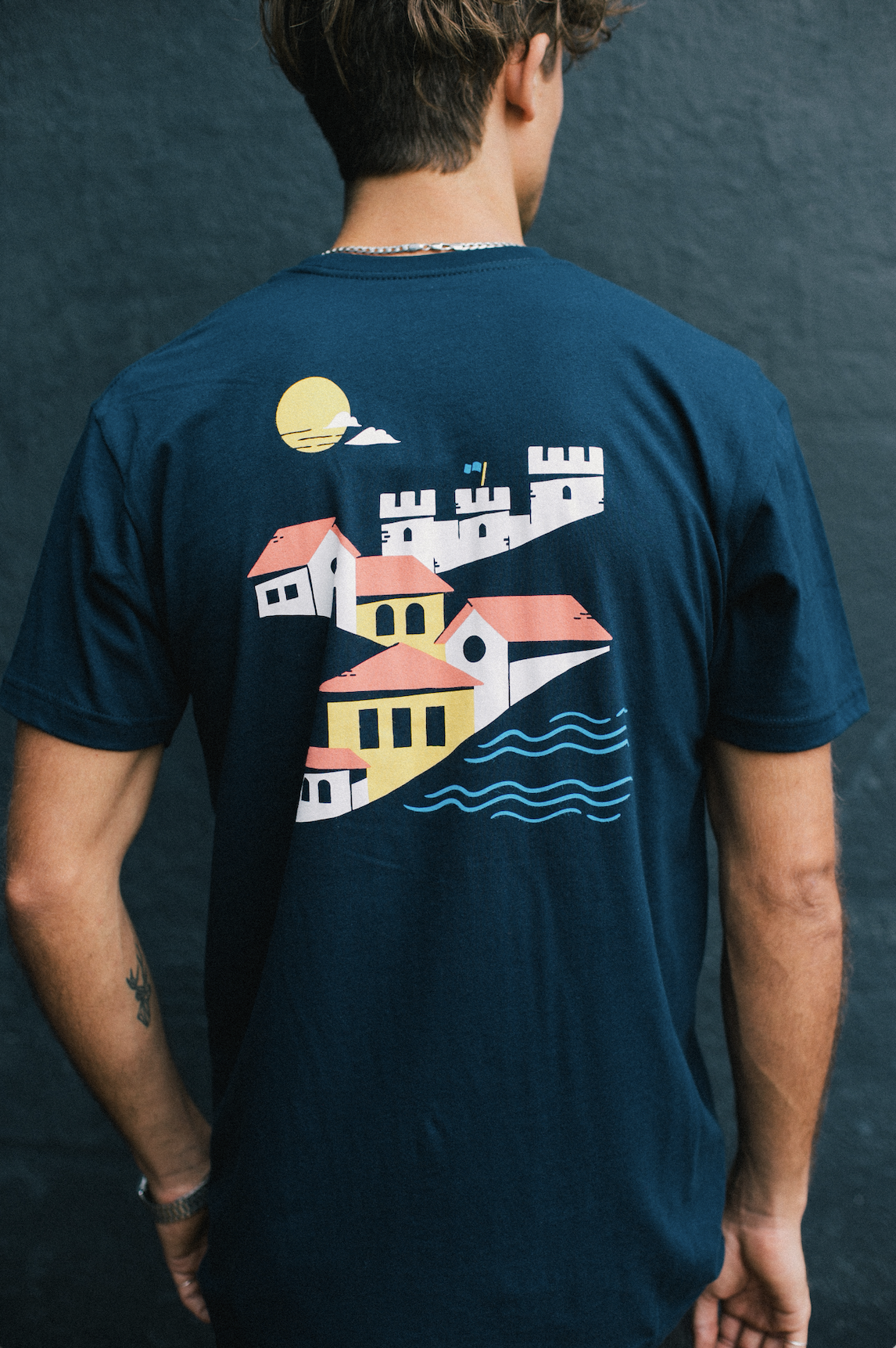 The back of a custom printed shirt with a beautiful colored seaside building.