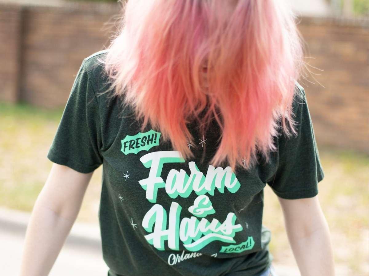 A pink haired girl wears a custom printed shirt.