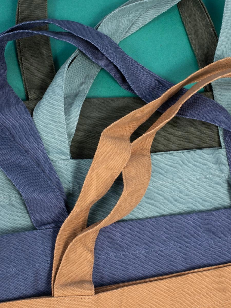 A stack of tote bags in neutral tones