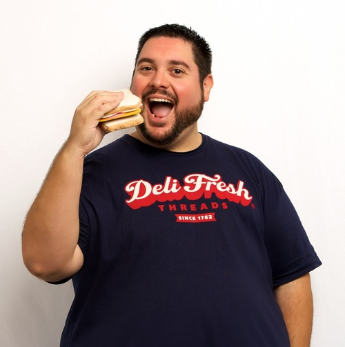 Large man holding a sandwhich to mouth