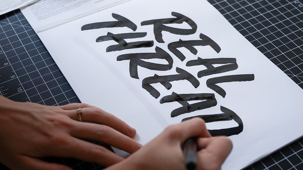 woman hand lettering words in black ink
