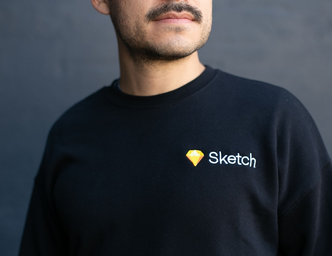 man with moustach wearing black sweater with sketch embroidery