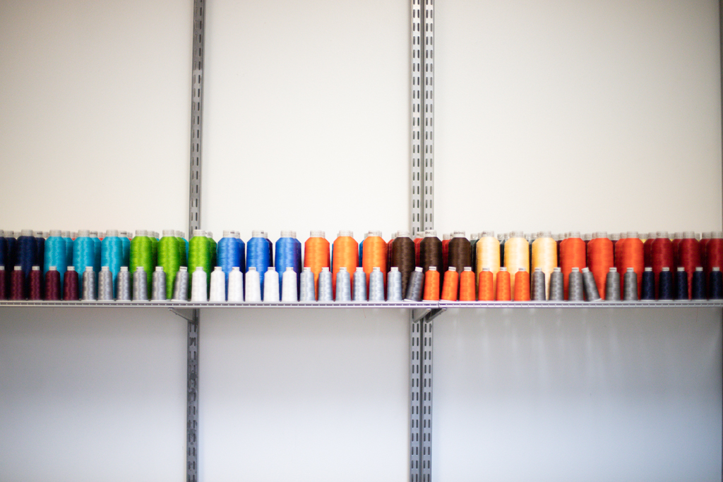 many different colored embroidery thread spools in line on a shelf