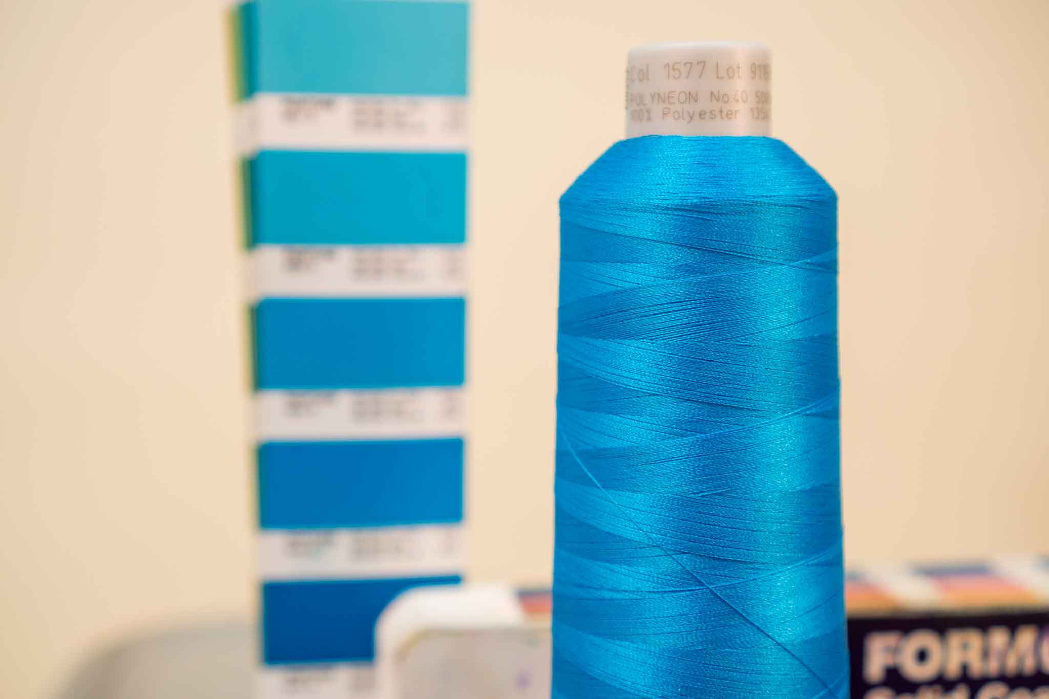 light blue embroidery thread spool in front of open blue pantone color swatch book