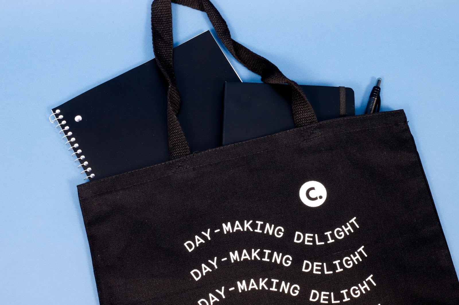 Corkcicle Black Custom Tote Bag Filled with Two Notebooks and a Pen