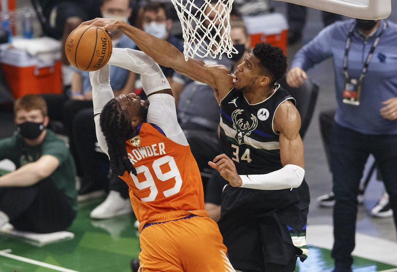 Basketball player blocking other player from scoring