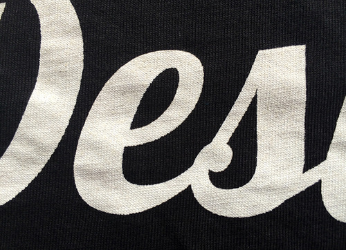 close up of white script graphic on black shirt
