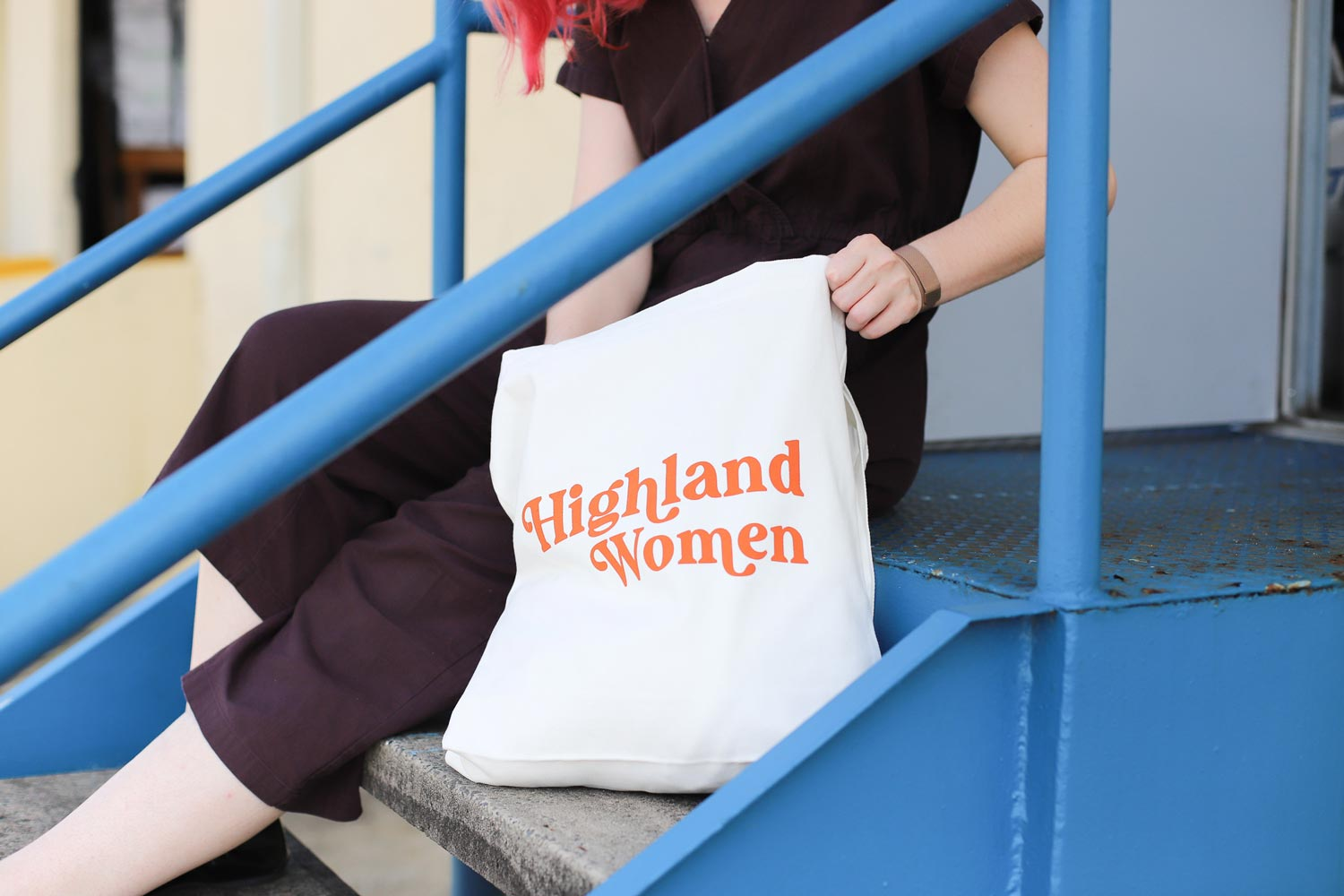 Woman in a dark romper on steps holding a white custom tote
