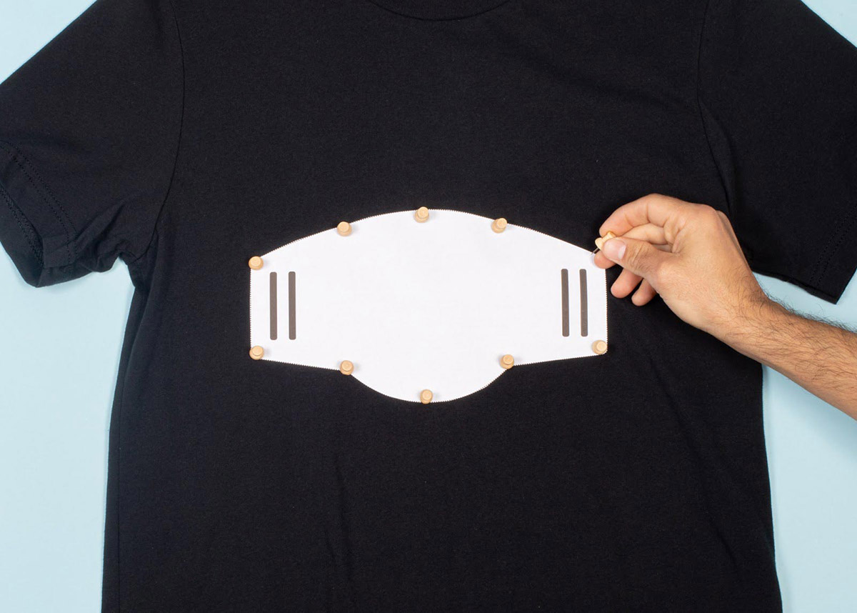 hand creating face mask out of shirt