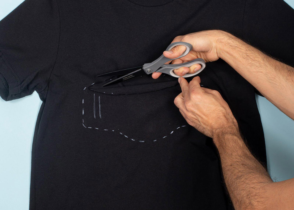 man cutting outline of face mask out of a shirt