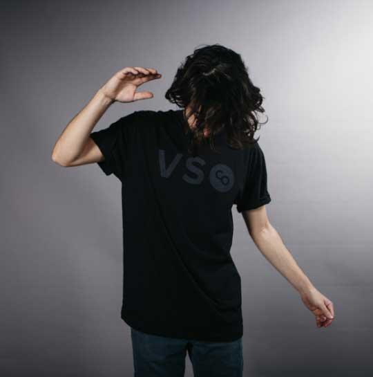 man with long hair modeling a black on black shirt