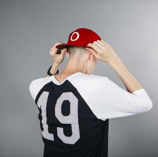 man wearing baseball hat pulling the red brim down
