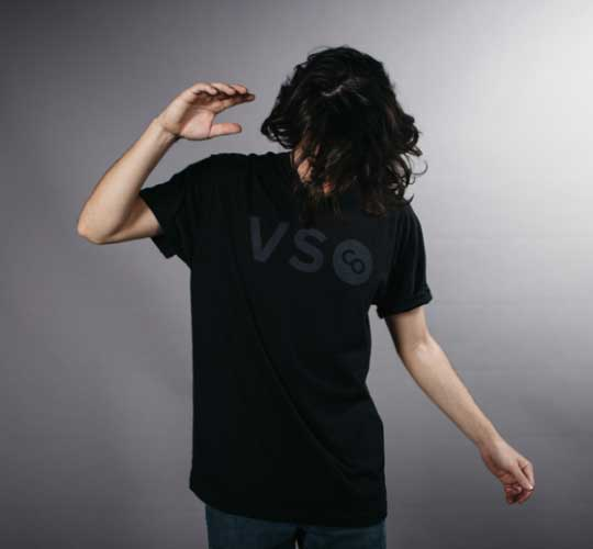 man standing with arms up wearing black shirt