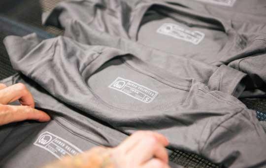 man inspecting tag printed shirts