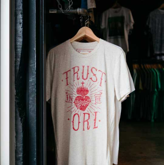 white shirt with red graphic hanging in closet