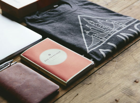 journal, laptop and shirt on wooden table