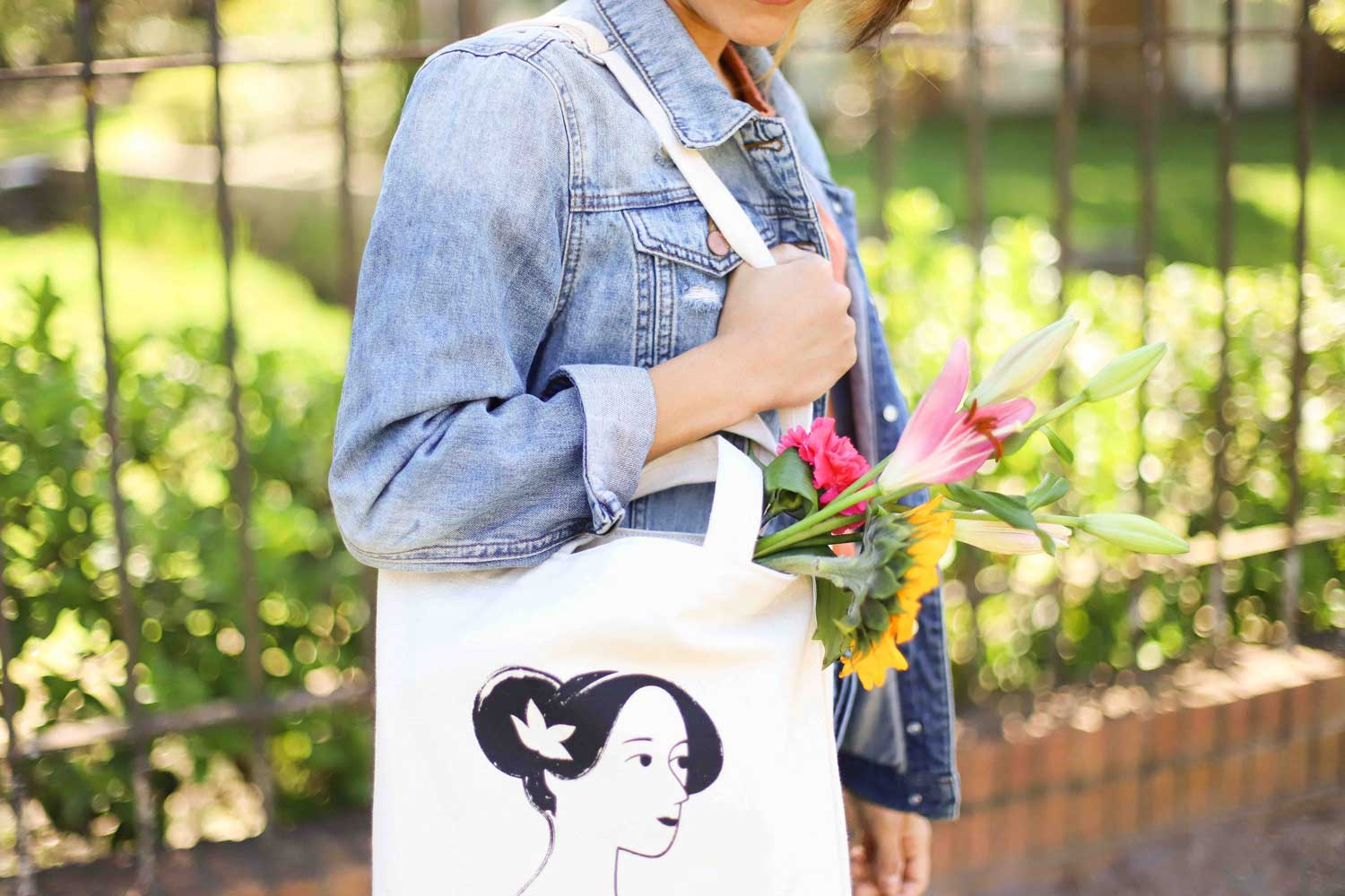 Woman in jean jacket carrying white tote with flowers in it