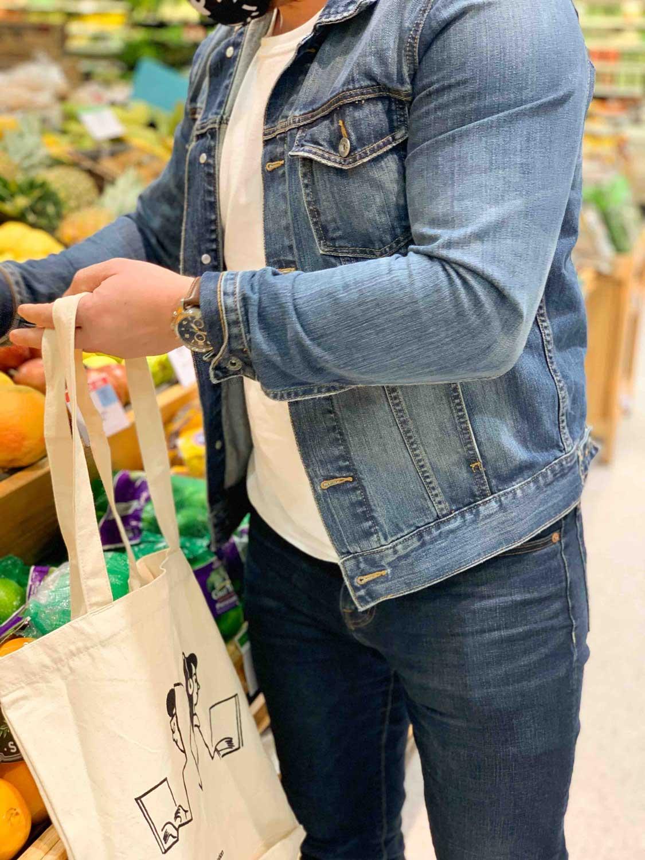 man using tote to grab fruit