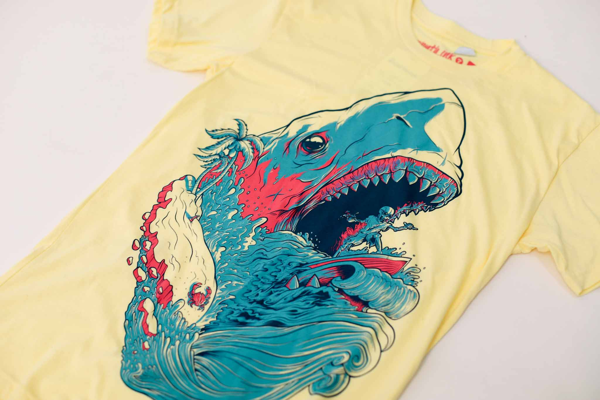 Yellow shirt with artwork of blue and pink shark with skeleton surfing in its mouth