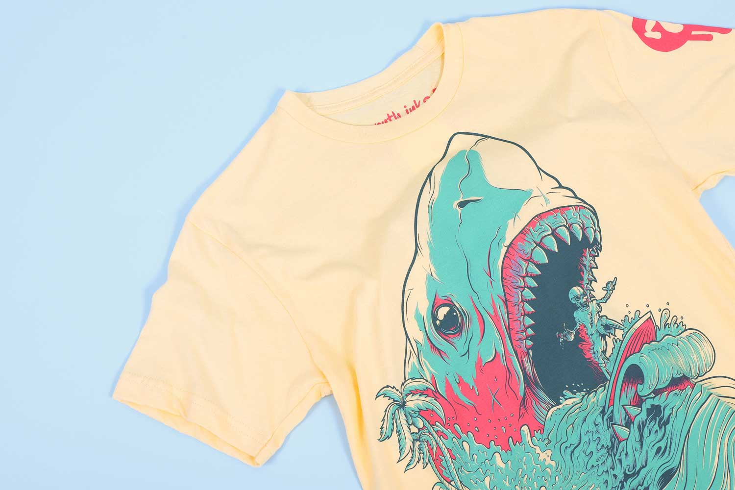 yellow shirt with blue and pink stylized shark and a skeleton riding a surfboard out of its mouth