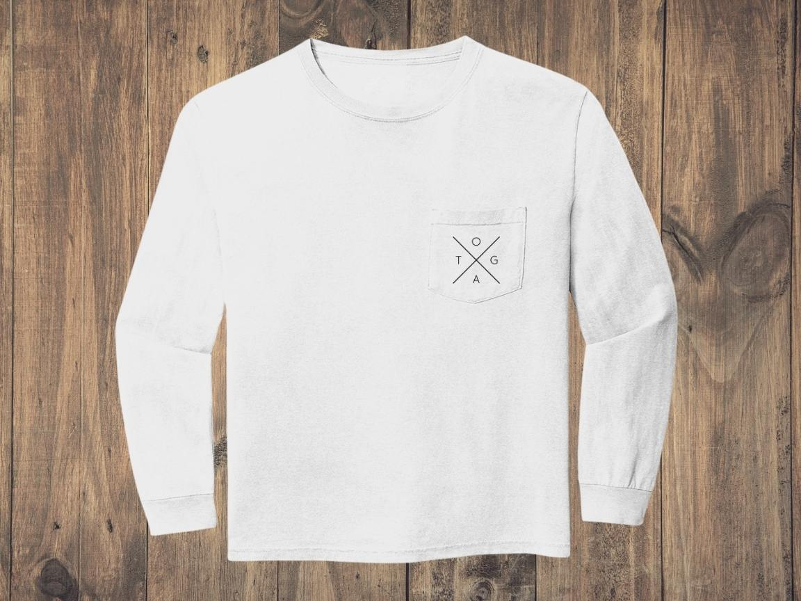 White sweatshirt with black X logo on front pocket against a wood background